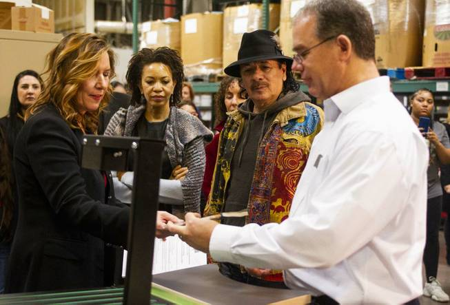 Executive Director/Co-Founder Lisa Habighorst, left, and Director of Operations David Ortlipp, right, of Spread the Word Nevada demo a book sorting machine for Carlos Santana, center right, and his wife Cindy Blackman, center left, during a tour of the Spread the Word facilities at their warehouse in Henderson, NV, Thursday, Jan. 17, 2019. The Milagro Foundation made a donation to Spread the Word, which will provide about 15,000 books to 57 schools across Southern Nevada.