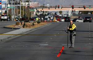 A member of Metro Police Department's fatal detail takes measurements at a fatal auto -pedestrian accident on Alta and Decatur Boulevard Thursday, Feb. 7, 2018.