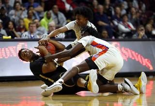 Clark High School's Antwon Jackson (23) fights for the ball with Bishop Gorman players Zaon Collins (10), top, and William McClendon (1) during the Class 4A state high school basketball championship at the Orleans Arena Friday, March 1, 2019.