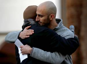 Co-organizer RJ Khalaf, right, gets a hug from Imam Fateen ...