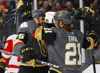 Vegas Golden Knights right wing Ryan Reaves, left, celebrates after center Cody Eakin, right, scored against the Detroit Red Wings during the second period of an NHL hockey game Saturday, March 23, 2019, in Las Vegas.