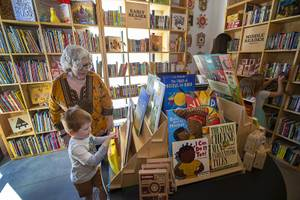 Amy Ayoub and Michael Alarid, 3, look though an Early Readers section during the launch of The Lucy and the grand opening of the new Writer's Block Book Shop & Coffee Shop at Sixth Street and Bonneville Avenue in downtown Las Vegas Saturday, April 13, 2019. The Lucy features 12 residential units built around the book store and an event space.