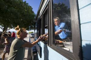 Andy Ross hands food to Christina Young from the Goodness Gracious Ministries food truck in Henderson on Monday, May 6, 2019.
