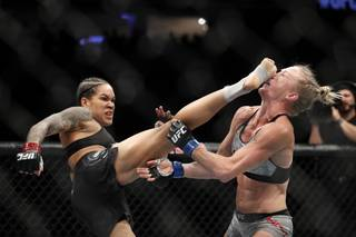 UFC bantamweight and featherweight champion Amanda Nunes of Brazil lands a kick on Holly Holms that knocks her to the mat in the first round of their bantamweight title fight during UFC 239 at T-Mobile Arena Saturday, July 6, 2019.