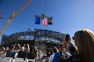 Attendees watch as the final iron beam is lowered during a topping off ceremony at the Raiders' stadium, Monday, Aug. 5, 2019.