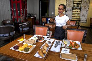 Co-owner Mini Yohannes poses behind an Ethiopian meal at NU Ethiopian Kitchen, 4230 S. Decatur Blvd., Tuesday, Aug. 6, 2019.