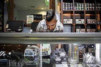 In this June 27, 2017, file photo, Jerred Kiloh, owner of the licensed medical marijuana dispensary Higher Path, stocks shelves with with cannabis products in Los Angeles. Weedmaps a major online pot shop directory and cannabis marketplace announced Wednesday, Aug. 21, 2019, that it will no longer allow black-market businesses to advertise on its site, a decision that could boost California's efforts to rein in its vast illegal market. Kiloh, who heads the United Cannabis Business Association, an industry group, projected that half of California's illegal operations could dry up once they are denied access to Weedmaps ads.