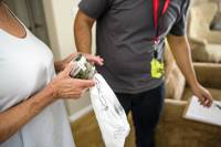 A customer receives a delivery of medical marijuana at her home July 12, 2017. The MedMen cannabis company has begun a 24-hour delivery service in Southern Nevada.