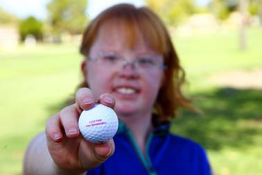 In this Aug. 28, 2019, photo, Amy Bockerstette, the golfer with Down syndrome who was an internet sensation by making par at the 16th hole at the Phoenix Open with soon-to-be 2019 U.S. Open champion Gary Woodland, smiles as she holds up a personalized logo golf ball after her golf lesson at Palmbrook Country Club in Sun City, Ariz.