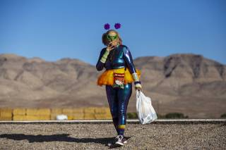Lucinda Clark, 59, from West Palm Beach, Florida, smokes a cigarette outside the entrance to the Storm Area 51 Basecamp in Hiko, Nevada, Friday, Sept. 20, 2019.